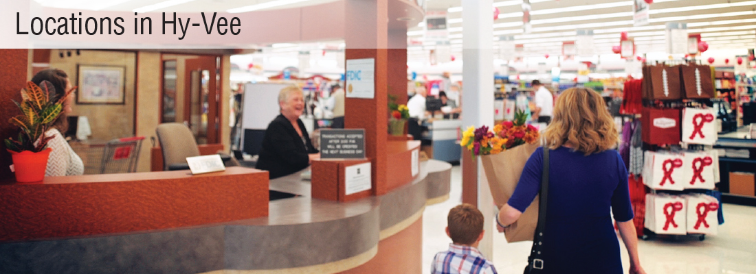 Woman and child walking past bank in grocery store.
